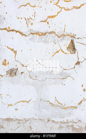 White scratched plaster wall background. Old wall with holes in plaster. Rough cracked stucco surface texture. Vertical photo - Stock Photo