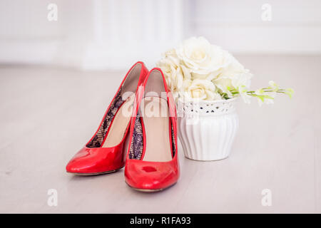 A bouquet of white roses in a vase and shoes. Wedding preparations. Wedding Attributes - Stock Photo