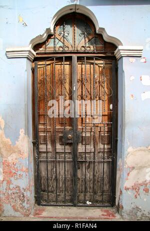 Central American weathered wooden door in a sky blue wall with metal grate covering - Stock Photo
