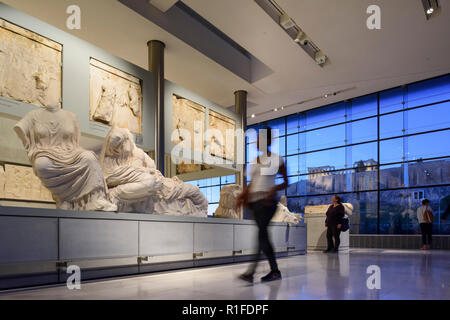 Athens. Greece. Interior of the Acropolis Museum at dusk with the Parthenon visible in the background. Mouseio Akropolis.  Building designed by Bernar - Stock Photo
