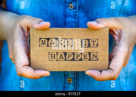 Woman hand holding cardboard card with words Make It Happen made by black alphabet stamps. Denim backgrounds. - Stock Photo