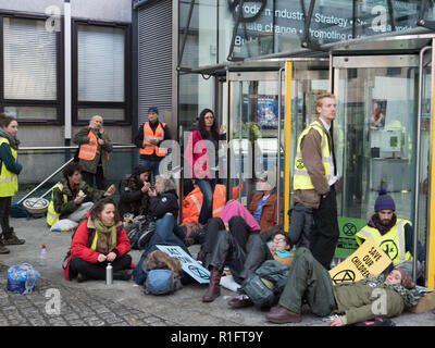 London, UK. 12th November 2018. Protesters of Extinction Rebellion holding a peaceful demonstration in front of the Department for Business, Energy & Industrial Strategy. Police have closed part of Victoria Street. Some protesters laying in front of the entrance to the Department. Credit: Joe Kuis / Alamy Live News - Stock Photo
