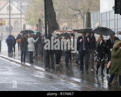 London, UK. 12th November 2018. Torrential rain downpour with some lightning and thunder at Parliament Square, after one o'clock, this early afternoon in autumn, soaking tourists and Londoners who are looking for cover. Credit: Joe Kuis / Alamy Live News - Stock Photo
