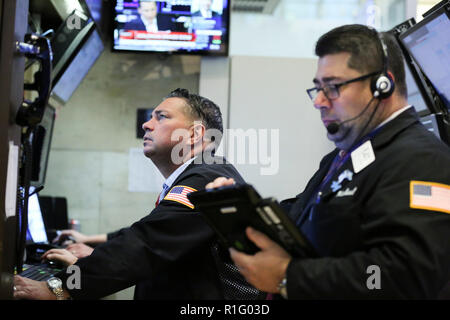 New York, USA. 12th Nov, 2018. Traders work at the New York Stock Exchange in New York, the United States, Nov. 12, 2018. U.S. stocks closed sharply lower on Monday, as steep losses in Apple shares led the tech rout, dragging the market. The Dow Jones Industrial Average slumped 602.12 points, or 2.32 percent, to 25,387.18. Credit: Wang Ying/Xinhua/Alamy Live News - Stock Photo
