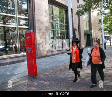 CHARLOTTE, NC, USA-10/31/18:  Two women, one in Halloween dress shows delight at being photographed, while her grumpy friend looks straight ahead. - Stock Photo
