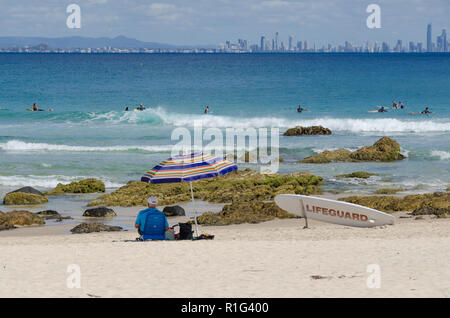 Lifeguard sits on beach in the shade of a umbrella watching surfers, with city skyline of Surf Paradise in background. - Stock Photo