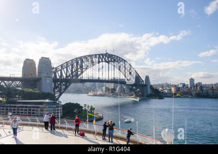 Passengers admire the beautiful iconic view of the Sydney Harbour Bridge from the deck of cruise ship docked at Sydney Cove Passenger Terminal. - Stock Photo