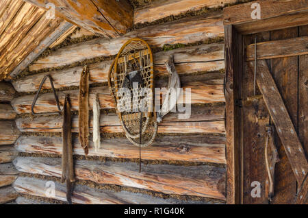 Closeup of exterior front porch of old rustic log cabin line snowshoes and animal furs. Frontier wilderness log cabin. - Stock Photo