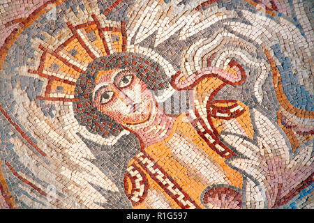 Ancient byzantine natural stone tile mosaics with face of mythical goddess and floral ornament, Madaba, Jordan - Stock Photo
