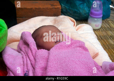 A new born infant is sleeping on a sidewalk in front of an urban slum building in Kampong Cham, Cambodia. - Stock Photo