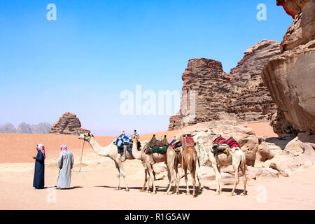 Two bedouins in traditional clothing with four camels dromedary in Wadi Rum desert, Jordan, Middle East - Stock Photo