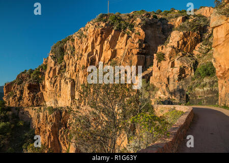 Road through taffoni rocks, orange porphyritic granite rocks, Les Calanche de Piana, UNESCO World Heritage Site, near town of Piana, Corsica, France - Stock Photo