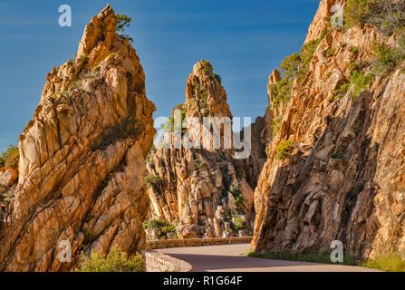 Taffoni rocks, orange porphyritic granite rocks, over road at Les Calanche de Piana, UNESCO World Heritage Site, near town of Piana, Corsica, France - Stock Photo