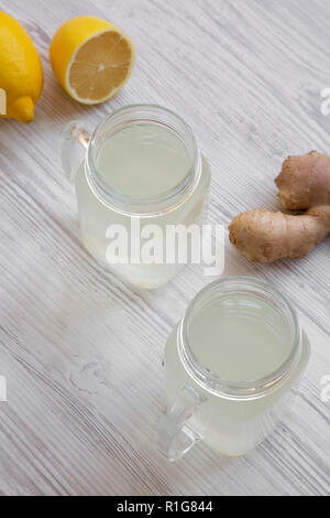 Homemade ginger tea with lemon in glass jars over white wooden background, high angle view. - Stock Photo