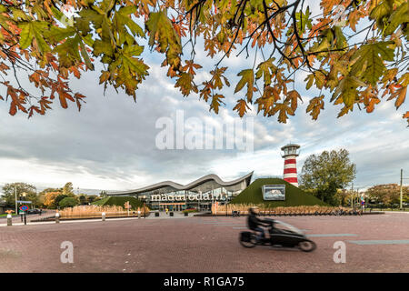 THE HAGUE, 7 November 2018 - Cyclist running fast in front of Madurodam miniature, the  park that shows most of the Dutch monuments under a clear clou - Stock Photo