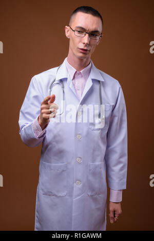 Young handsome androgynous man doctor against brown background - Stock Photo