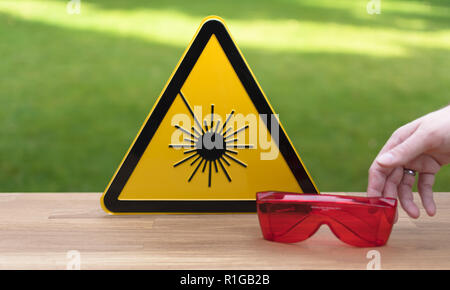 Laser safety sign and safety glasses - Stock Photo