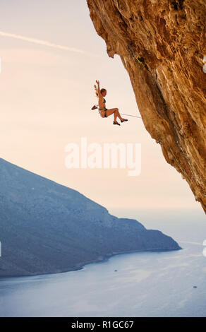 Female rock climber falling of a cliff while lead climbing at sunset - Stock Photo