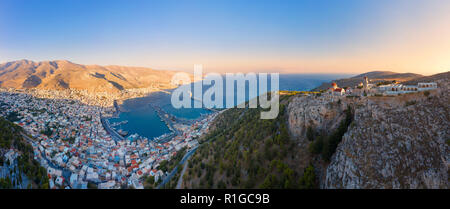 Panoramic view of Pothia Town, capital of Kalymnos, Greece, and Monastery of Agios Savvas located on top of hill, on left - Stock Photo
