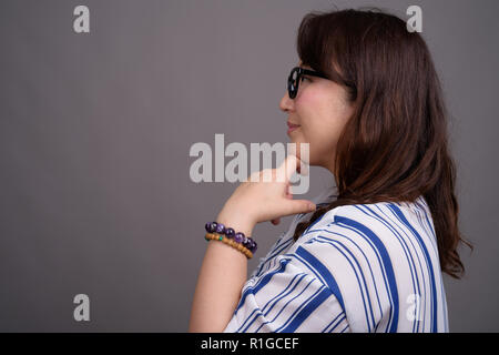 Portrait of mature Asian businesswoman wearing eyeglasses - Stock Photo