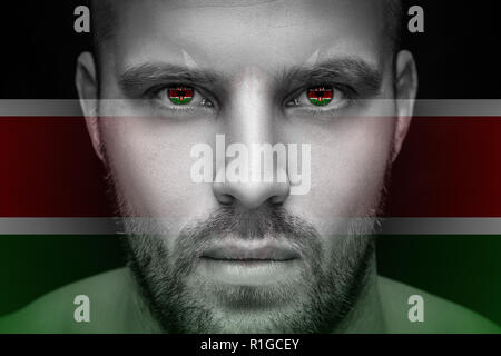 Portrait of a young serious man, in whose eyes the reflected national flag of Kenya, against an isolated black background and flag - Stock Photo