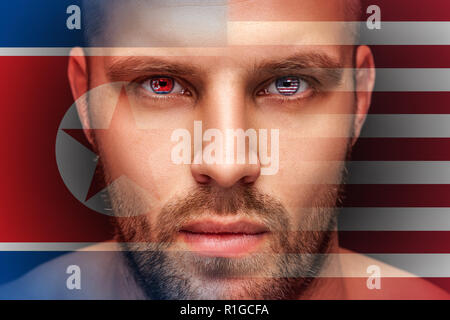 Portrait of a young serious man, in whose eyes the reflected national flag of Korea and America, against an isolated black background and flag - Stock Photo