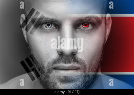 Portrait of a young serious man, in whose eyes the reflected national flag of North and South Korea, against an isolated black background and flag - Stock Photo