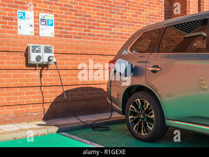 Mitsubishi outlander PHEV plugged in and charging at an EV Driver EV electric car charging point hybrid car charging Aldeburgh Suffolk England UK - Stock Photo