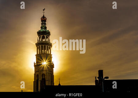 Sun rays through the Lange Jan Toren (Long John Tower) of the medieval Abbey from the Sun setting behind the tower in the Historic City of Middelburg - Stock Photo