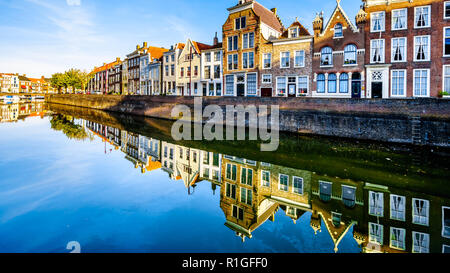 Sunset over a row of Houses that are reflecting on the water surface of a canal in the Historic City of Middelburg in Zeeland Province, the Netherland - Stock Photo