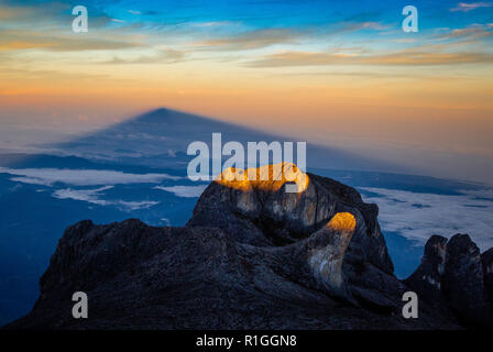 Sunrise on Mount Kinabalu casting a shadow of the mountain on distant mists - Sabah Borneo Malaysia - Stock Photo