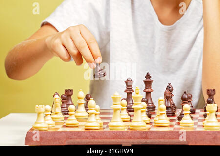 Kid sitting near chessboard and play chess game. - Stock Photo