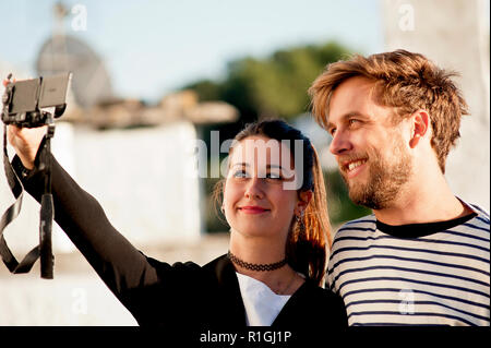 An attractive young couple take a selfie with their camera at Alberobello, a popular tourist destination in Puglia, southern Italy. - Stock Photo