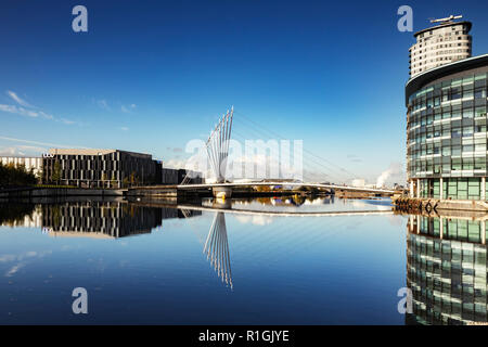 2 November 2018: Salford Quays, Manchester, UK - Media City Footbridge, reflected in the Manchester Ship Canal. - Stock Photo