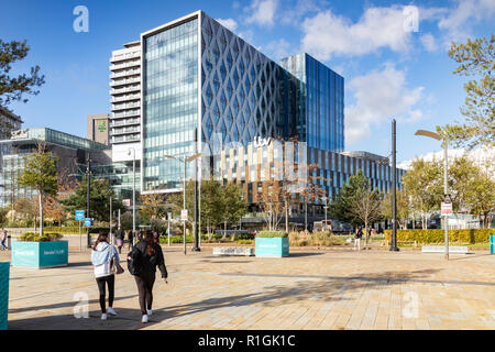 2 November 2018: Salford Quays, Manchester, UK - ITV buildings on a sunny autumn day, clear blue sky, two young women walking towards building. - Stock Photo