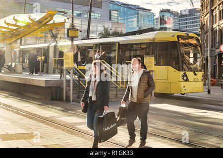 2 November 2018: Manchester, UK - Young couple smiling, with Debenhams shopping bags, in Exchange Square, with a Metrolink tram behind. Lots of flare. - Stock Photo