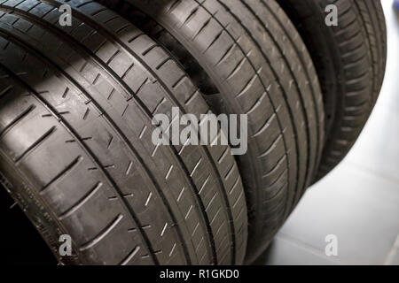 Tires for sale at a tire store and Stacks of old used tires and new one.all season car tires.Selective focus.Car service. all season car tires - Stock Photo