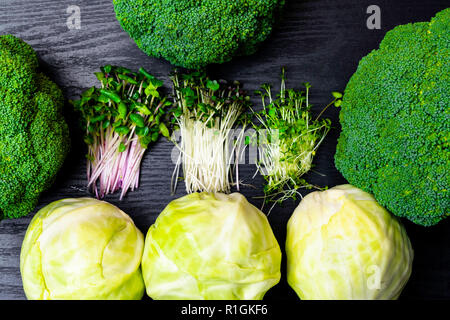 green vegetables frame, white cabbage, broccoli, greens sprouts isolated on wooden background top view