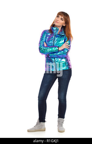 Skeptic young woman in vibrant and shiny down jacket, jeans and sneakers is standing with arms crossed and looking away. Front view. Full length studi - Stock Photo