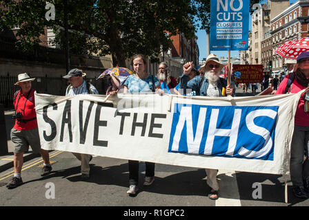70th anniversary rally to celebrate the founding of the NHS and protest against cuts with a large banner 'Save the NHS' - Stock Photo