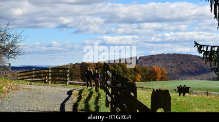 Couple walking paved trail along wooded fence in Fall - Stock Photo