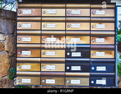 European aged metallic mailboxes on a stone wall. - Stock Photo