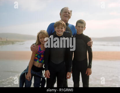 Smiling father standing with his three children in wetsuits. - Stock Photo