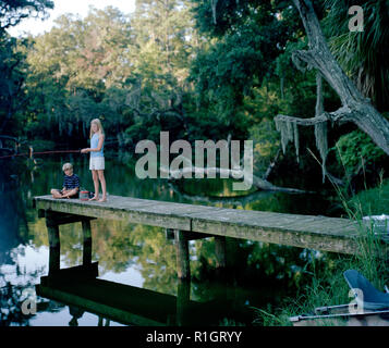 Smiling girl fishing off the edge of a small jetty with her brother at a lake. - Stock Photo