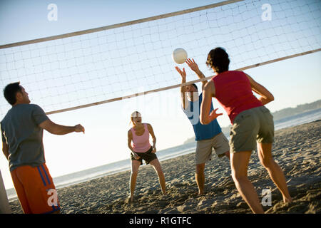 Two mid-adult couples playing volleyball on a beach. - Stock Photo