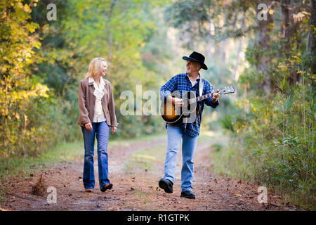 Mature man playing a guitar for his wife while walking along a country road. - Stock Photo