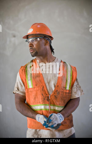Dirty mid-adult construction worker wearing a helmet and hi-visibility vest. - Stock Photo