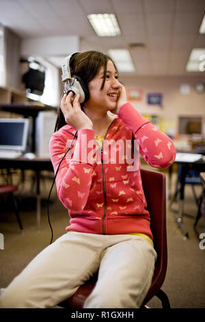 Smiling teenage girl in a classroom wearing headphones. - Stock Photo