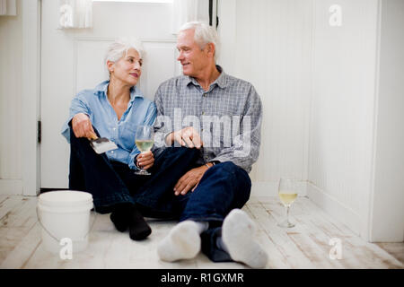 Senior couple relaxing with wine after house painting - Stock Photo