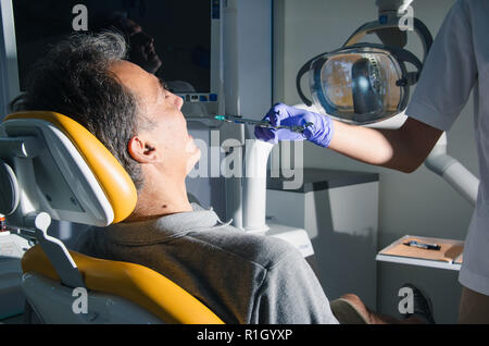 Nurse with syringe gives injection to a patient in dentist office. - Stock Photo